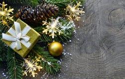 Décoration de Noël avec l'arbre de sapin, le boîte-cadeau d'or, les lumières de guirlande et les cônes de pin sur le vieux fond e Photographie stock libre de droits