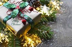 Décoration de Noël avec l'arbre de sapin, le boîte-cadeau, les lumières de guirlande et les cônes de pin sur le vieux fond en boi Images stock