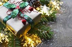 Décoration de Noël avec l'arbre de sapin, le boîte-cadeau, les lumières de guirlande et les cônes de pin sur le vieux fond en boi Photos stock