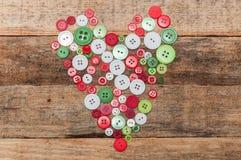 Décoration de Noël Boutonne le coeur sur le fond en bois Photographie stock
