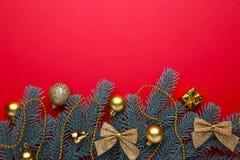 Décoration de Noël Branche de sapin avec des boules d'or, de petits cadeaux et des arcs sur un fond rouge photographie stock