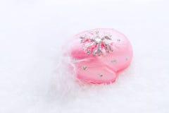 Décoration de Noël d'belles mitaines en verre roses sur la neige naturelle Photographie stock libre de droits
