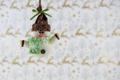 Décoration de Noël d'image de photographie de Noël raccrochant du bonhomme de neige avec le fond de papier d'emballage de renne Photos stock