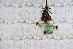Décoration de Noël d'image de photographie de Noël raccrochant du bonhomme de neige avec le fond de papier d'emballage de renne photographie stock libre de droits