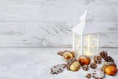 Décoration de Noël Lanterne sur la neige avec des glands et des feuilles de chêne Images stock