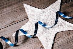 Décoration de Noël - ruban bleu sur l'étoile blanche Photographie stock