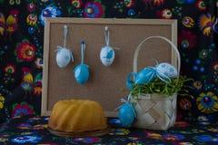 Décoration de Pâques avec les oeufs blancs et bleus sur le fond peint de textile avec le corkboard photographie stock