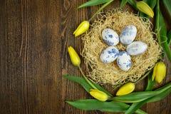 Décoration de Pâques des oeufs et des tulipes sur le fond en bois Images stock