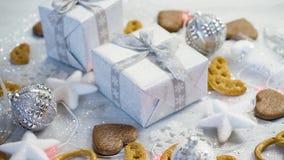 Décoration de table de Noël avec les cadeaux argentés, les babioles et les biscuits faits maison banque de vidéos