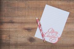 Décoration de vacances d'hiver avec la note blanche de Joyeux Noël et stylo rayé rouge et blanc sur le bois images libres de droits