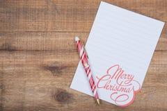 Décoration de vacances d'hiver avec la note blanche de Joyeux Noël et stylo rayé rouge et blanc sur le bois image libre de droits