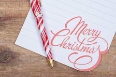 Décoration de vacances d'hiver avec la note blanche de Joyeux Noël et stylo rayé rouge et blanc sur le bois photo libre de droits