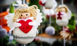 Décoration de vintage d'hiver Noël ou ange accrochant de Valentine petit avec un coeur rouge dans des ses mains images stock
