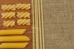 Décoration des pâtes Préparation de la nourriture faite maison Différents genres de pâtes sur le fond en bois Création du menu Images stock