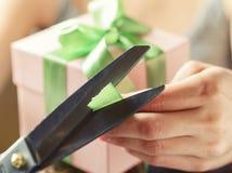 Décoration du boîte-cadeau avec le ruban vert utilisant des ciseaux photo libre de droits