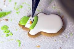Décoration du pain d'épice avec du sucre glace utilisant un sac pipping Biscuits faits main sous forme de bonhomme de neige Festi Photo stock