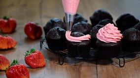 Décoration du petit gâteau de chocolat avec de la crème Serrage crème sur les petits gâteaux délicieux banque de vidéos