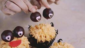 Décoration du petit pain drôle avec des yeux de chocolat et le sourire rouge Concept de Veille de la toussaint banque de vidéos