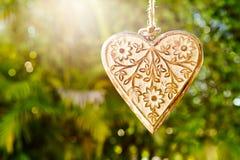 Décoration en bois de coeur avec la lumière du soleil rétro-éclairée contre le dos de vert Photo stock