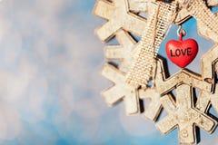 Décoration en bois de Noël de flocon de neige avec le petit coeur rouge sur le PS Image libre de droits