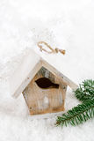 Décoration en bois de Noël de maison d'oiseau sur le fond de neige Photos stock