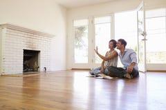 Décoration enthousiaste de planification de couples de nouvelle maison Photographie stock libre de droits