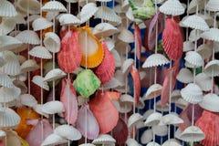 Décoration faite de coquilles colorées sur thred Photos stock