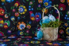 Décoration folklorique de Pâques de style avec les oeufs blancs et bleus sur le fond peint de textile photographie stock libre de droits