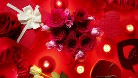 Décoration romantique de jour de valentines avec des roses, cadeaux enfermés dans une boîte, bougies banque de vidéos