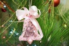 Décoration rose, qui a la forme de cloche, sur l'arbre de Noël Photo stock