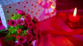 Décoration Valentine avec le bouquet de fleur, la combustion de bougie et les boîte-cadeau clips vidéos
