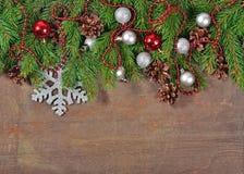 Décorations argentées et rouges de Noël et branche et cônes impeccables Images stock