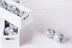 Décorations argentées molles de Noël dans des boîtiers blancs sur un fond en bois blanc Photos stock
