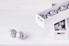 Décorations argentées molles de Noël dans des boîtiers blancs sur un fond en bois blanc Photo stock