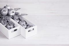 Décorations argentées molles de Noël dans des boîtiers blancs sur un fond en bois blanc Photos libres de droits