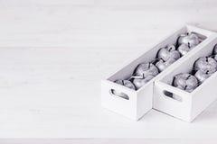 Décorations argentées molles de Noël dans des boîtiers blancs sur un fond en bois blanc Photographie stock libre de droits