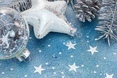 Décorations d'arbre de Noël sur le fond bleu de scintillement avec l'étoile Images libres de droits