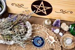 Décorations d'autel de sorcière - avec le pentagramme, les herbes et les cristaux, avec le tissu naturel d'autel de jute de noire photo stock