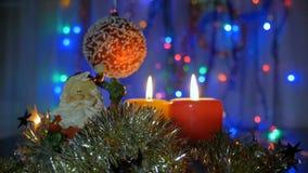 Décorations d'an neuf et de Noël Bougies brûlantes Guirlandes de clignotant Fond brouillé Une belle boule rouge banque de vidéos