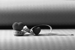 Décorations de coeur et règle flexible se trouvant sur le tapis de yoga Image stock