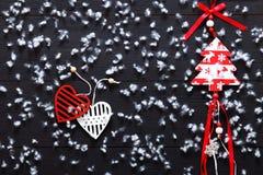 Décorations de Joyeux Noël, flocons de neige, coeurs rouges blancs et arbre de Noël de jouet sur la carte en bois noire de fond,  Photo stock