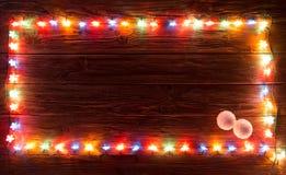 Décorations de lumière de Noël sur la texture en bois photos stock