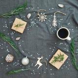 Décorations de Noël, branche d'arbre à feuilles persistantes, tasse de café et cadeaux sur le plaid gris Configuration plate, vue image libre de droits