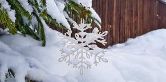 Décorations de Noël couvertes de neige blanche sous forme de flocons de neige sur un arbre de Noël vert neigeux dans une forêt de photos stock