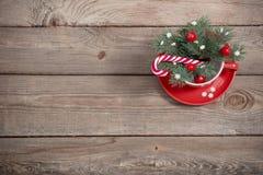 Décorations de Noël dans la tasse rouge sur le fond en bois image libre de droits