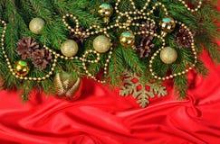 Décorations de Noël et branche et cônes impeccables sur un rouge Photo libre de droits