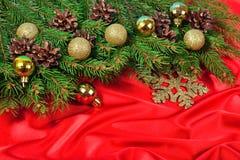 Décorations de Noël et branche et cônes impeccables sur un rouge Photos stock