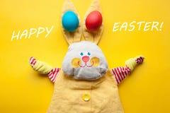 Décorations de Pâques d'un lapin fait main de jouet et des oeufs colorés sur un fond orange Avec les mots Joyeuses Pâques Photos libres de droits