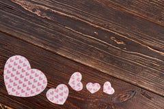 Décorations en forme de coeur de papier sur le fond en bois Photographie stock
