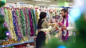Décorations et cadeaux de achat de Noël de couples affectueux heureux pour Noël banque de vidéos